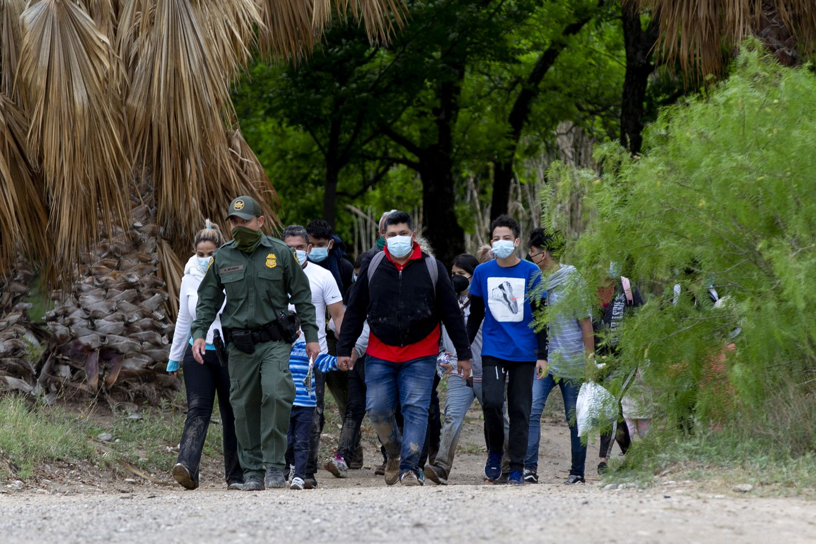 Un agente de la Patrulla Fronteriza y Aduanas de los Estados Unidos guía a un grupo de migrantes, en su mayoría de Venezuela, después que cruzaron el Río Grande cerca de Del Rio, Tx., El jueves 29 de abril de 2021 (Jessica Phelps / San Antonio Express- Noticias)