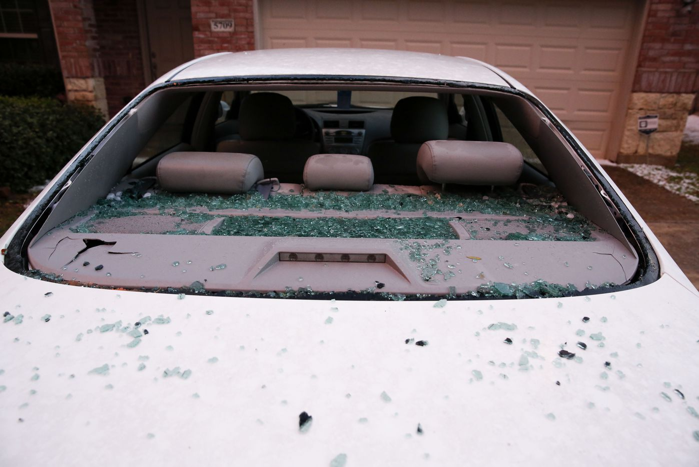A car with a broken windshield after hail pounded houses and cars in the City of McKinney as a severe storm passed through on Sunday, March 24, 2019.