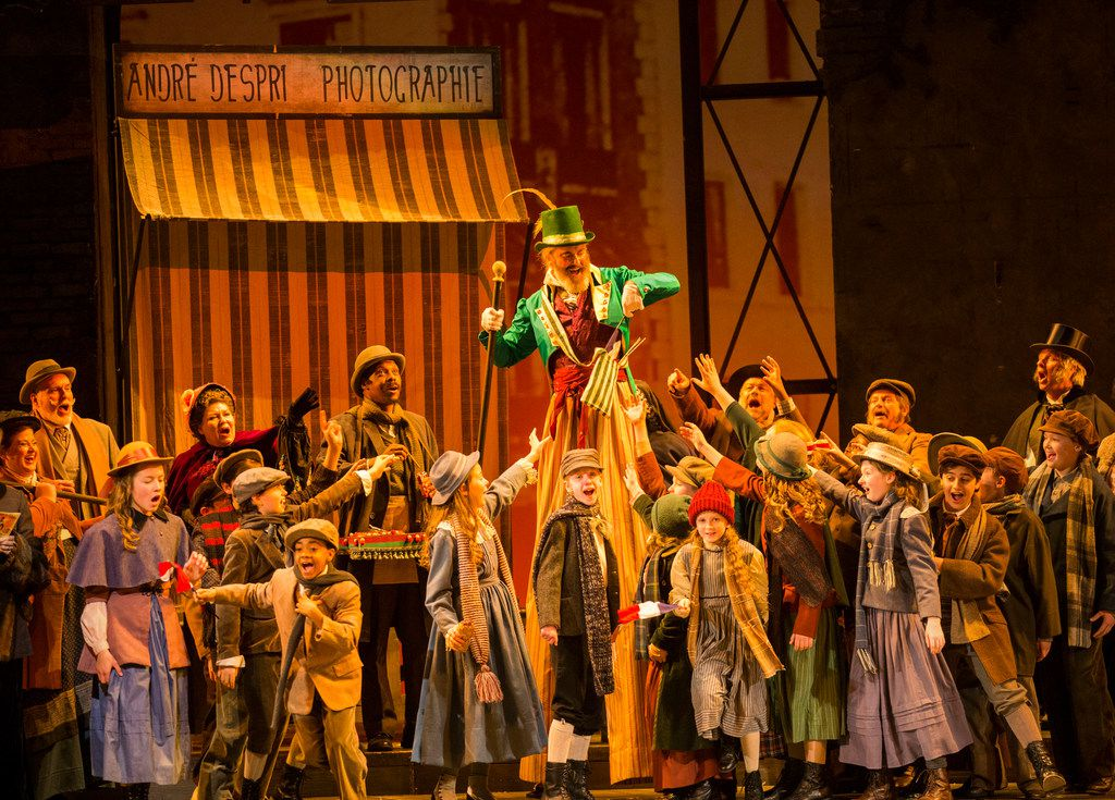 Parpignol, played by Don LeBlanc (center) hands French flags to children in Act 2 during the final dress rehearsal of La boheme presented by the Dallas Opera at the Winspear Opera House at the AT&T Performing Arts Center in Dallas on March 12, 2019.
