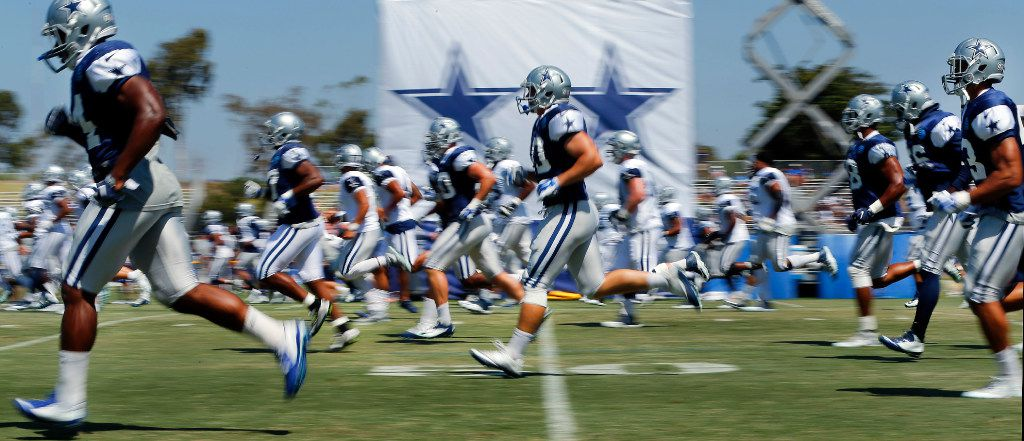 Cowboys players sprint down the field as the warm up for morning practice at training camp in Oxnard, Calif., on Aug. 11, 2016.