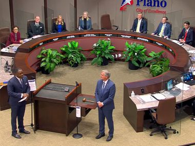 Plano's outgoing mayor, Harry LaRosiliere (front left) talks with new Mayor John Muns during a swearing-in ceremony on May 10, 2021 at the city council chambers.