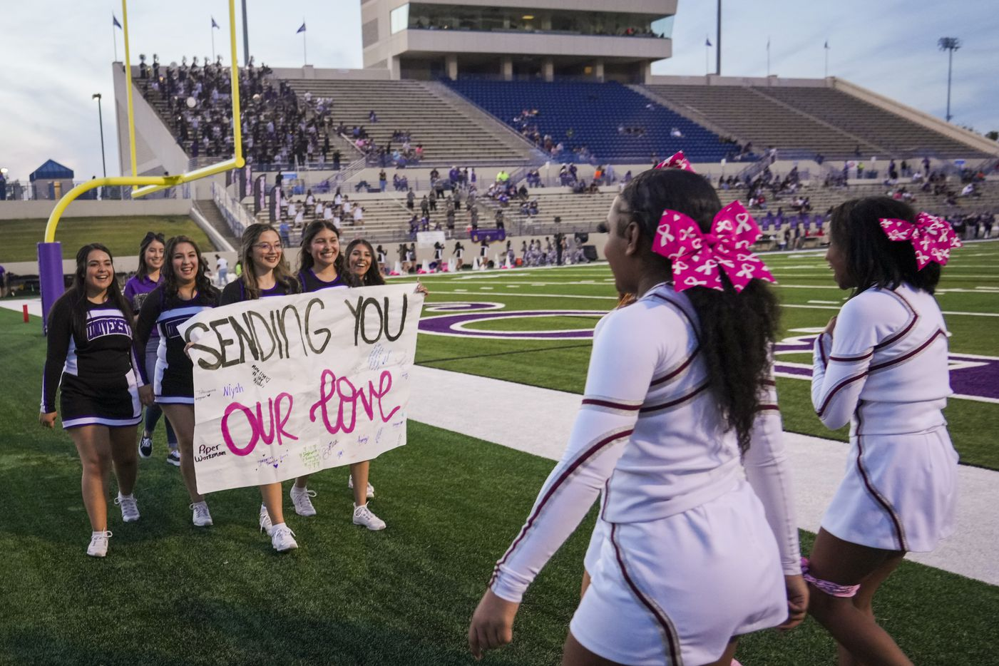 """Mansfield Timberview cheerleaders (right) are met by their counterparts from Waco University High School who presented them with a banner reading """"Sending You Our Love"""" before a high school football game at Waco ISD Stadium on Friday, Oct. 8, 2021, in Waco, Texas."""
