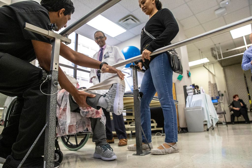 Physical therapist Binu Aramath (left) helps Hareg Wolde's mother as neurologist Dr. Mehari Gebreyohanns and Wolde watch at Parkland Hospital in Dallas.