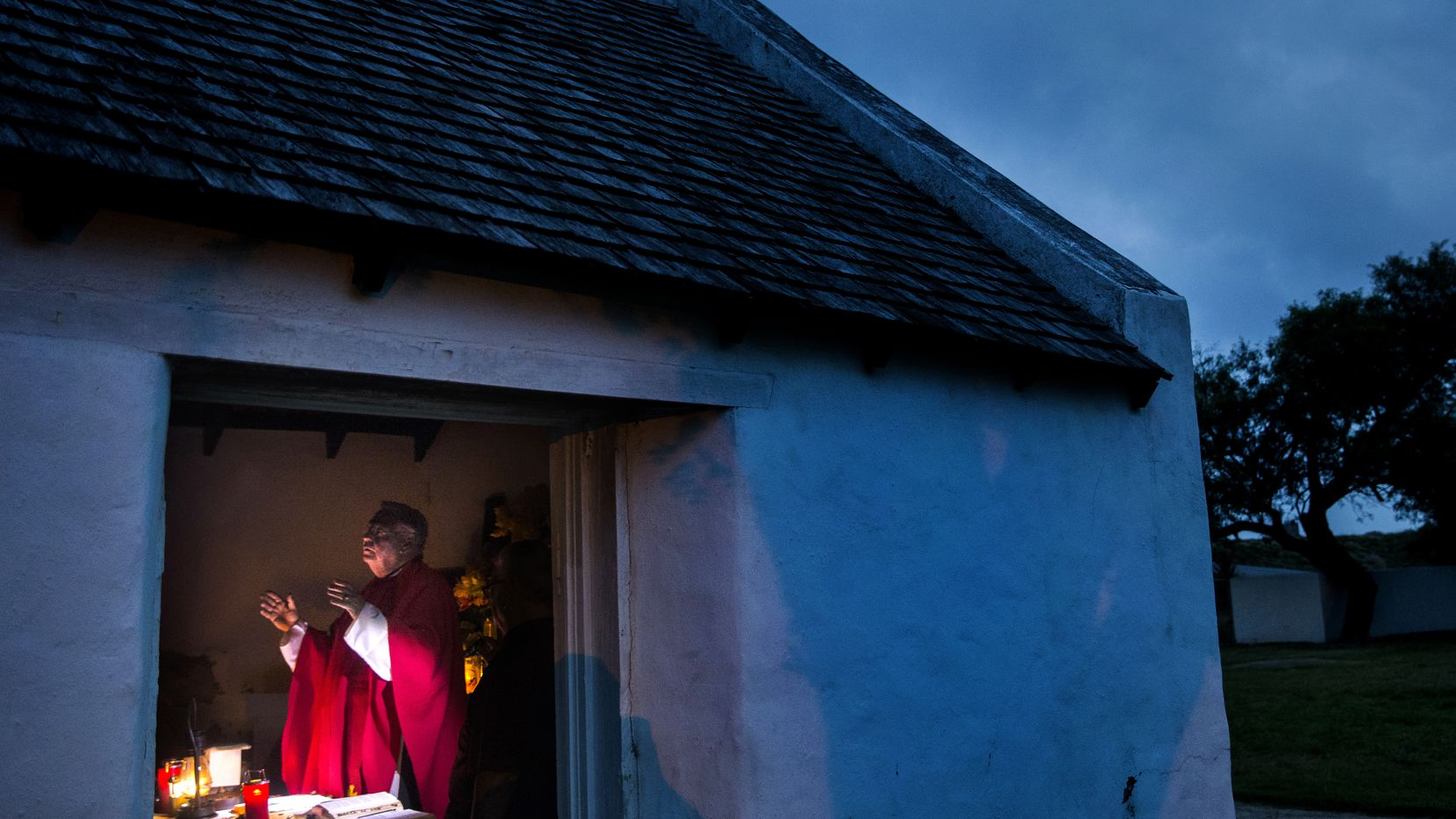"""As the sun begins to rise, Father Roy Snipes opens a sunrise Mass at La Lomita chapel near Mission. Snipes began holding Mass each Friday at 6:55 a.m. last fall to ask for divine intervention for those seeking asylum. """"When we come out here in the morning and you see the sun begin to peak up and you hear the birds chirping, it's a special experience that brings you back to our roots in this land,"""" said Snipes."""