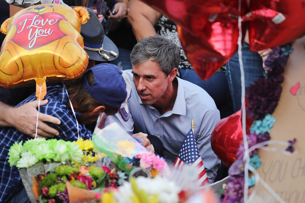 Democratic presidential candidate and former Rep. Beto O'Rourke consoles Antonio Basbo, who was mourning the loss of his common-law wife, Margie Reckard, at a makeshift memorial outside the Walmart in El Paso where a mass shooting left 22 people dead,