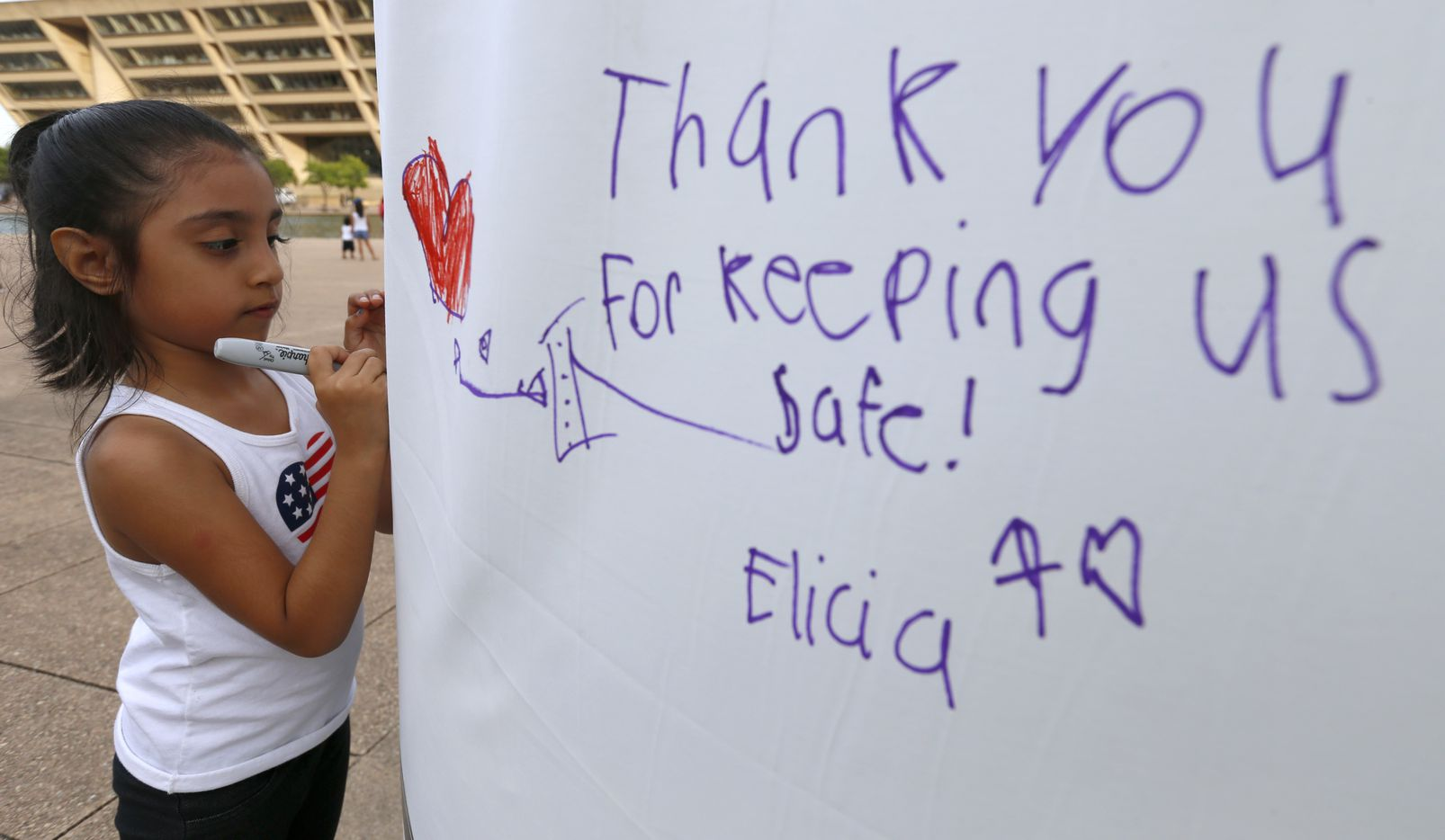 Janice Depaz, 5, writes a message next to other tributes during the Tribute 7/7 memorial event.