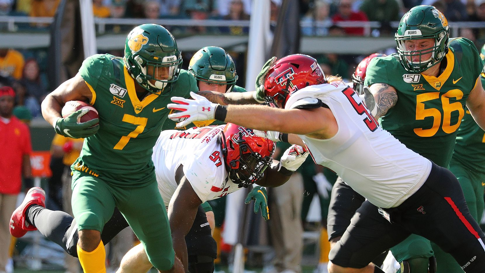WACO, TEXAS - OCTOBER 12: John Lovett #7 of the Baylor Bears tries to hold off Eli Howard #53 of the Texas Tech Red Raiders in the first half on October 12, 2019 in Waco, Texas.