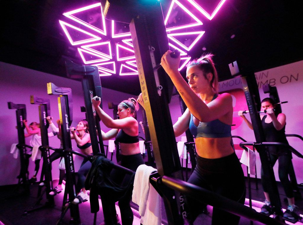 Jennifer Cantelmo (right) works out on the VersaClimber, as lights and music create an energized atmosphere.