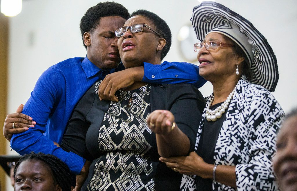 (from left) Brandt Jean, 15, and his mother Allison Jean -- who are the brother and mother of Botham Jean -- mourn with another churchgoer during a prayer service for Botham at the Dallas West Church of Christ on Sunday, September 9, 2018. Botham Jean was shot and killed by Dallas police officer Amber Guyger in Jean's apartment the previous Thursday night.