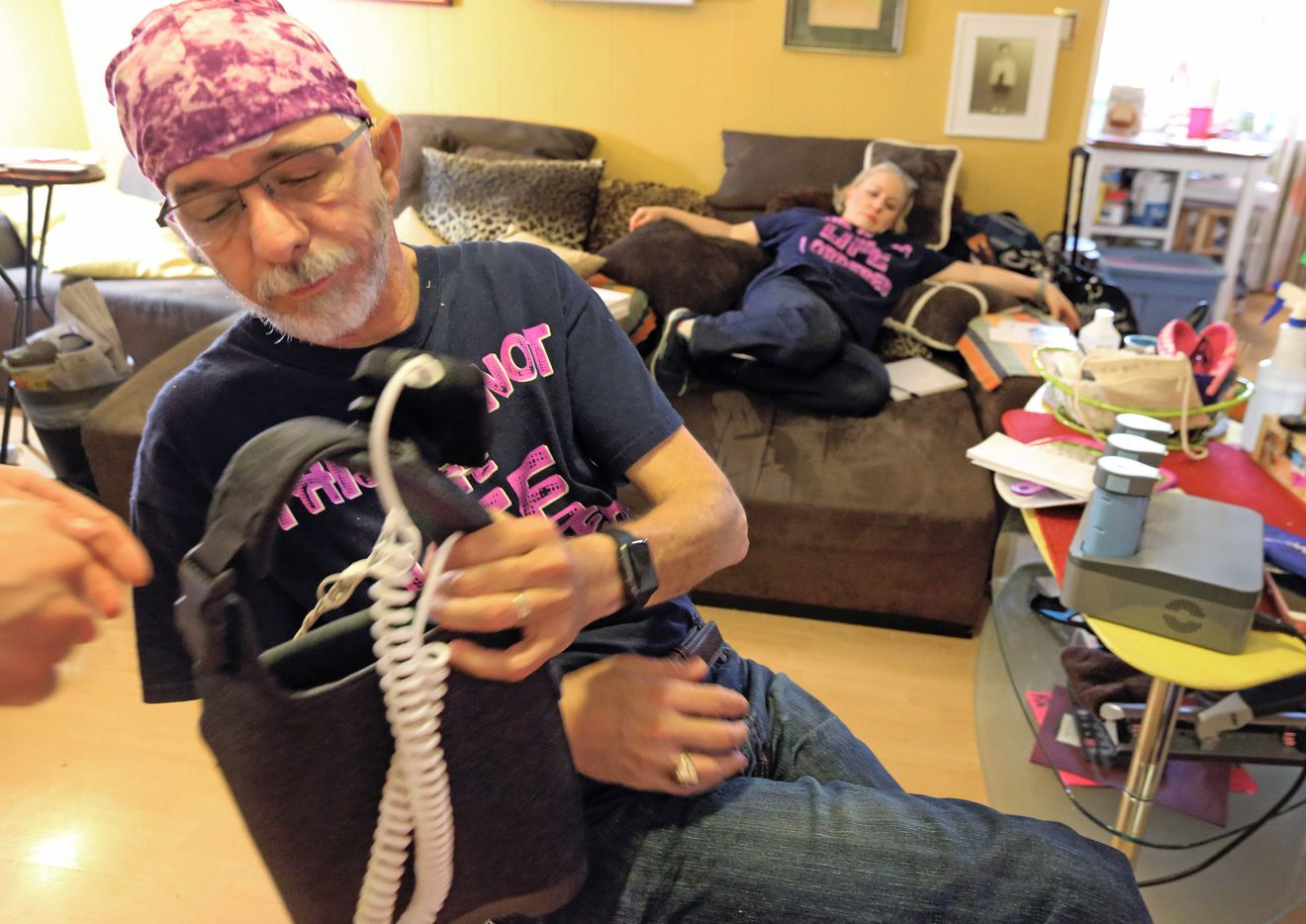 Jeffrey Weiss familiarizes himself with the Optune device he was using for treatment, as his wife Marni relaxes for a moment at their home in Dallas.