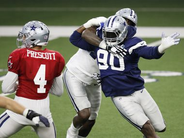 Cowboys defensive end DeMarcus Lawrence (90) rushes quarterback Dak Prescott (4) as he is blocked by offensive tackle Cameron Erving (75) on a play during training camp at The Star in Frisco on Friday, Aug. 28, 2020.
