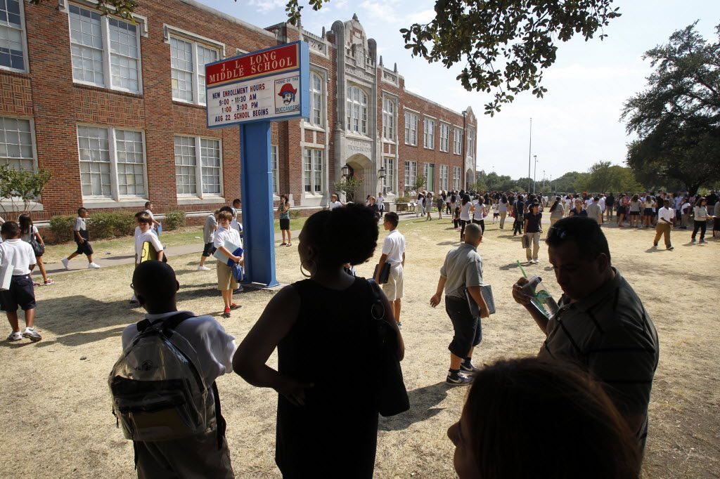 Parents wait for their children under the shade of a large oak tree on the first day of school at Dallas ISD's J. L. Long Middle School in Dallas on August 22, 2011.