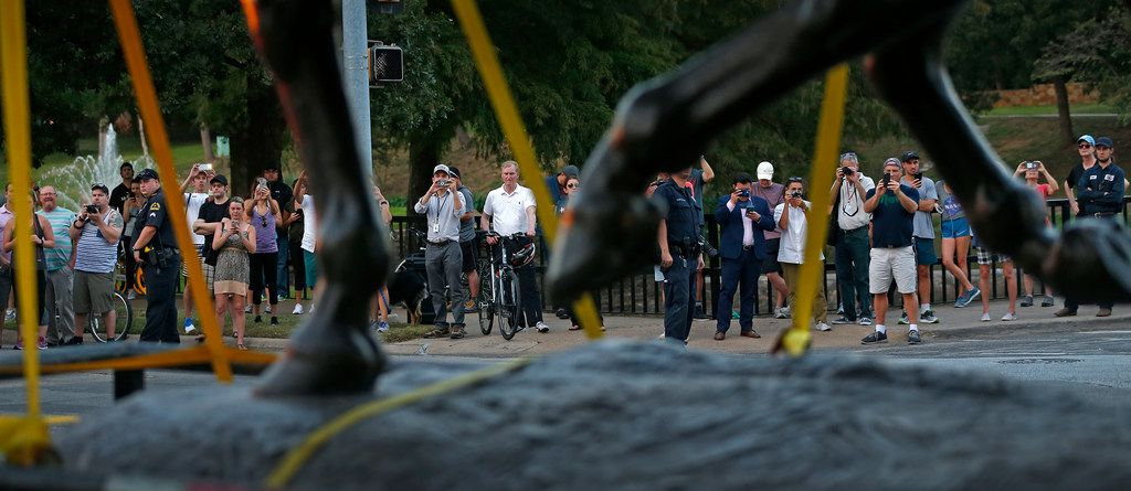 People watch the Robert E. Lee statue being carried on a truck at Robert E. Lee Park in Dallas, Thursday, Sept. 14, 2017.