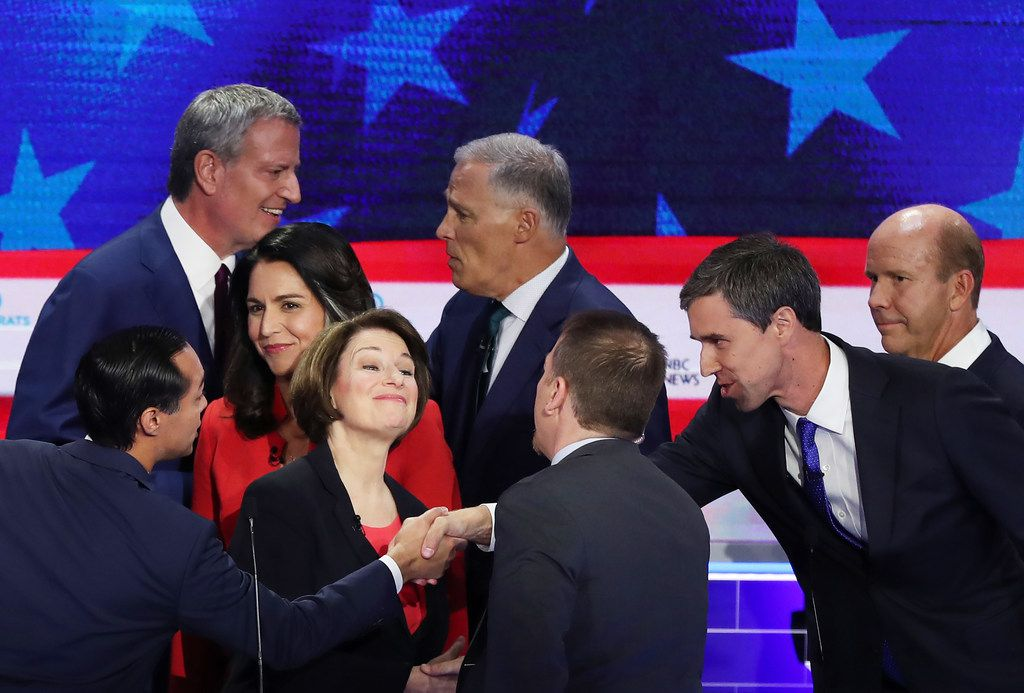 Julian Castro and Beto O'Rourke shake hands after the first Democratic presidential debate on June 26, 2019 in Miami, crossing arms between moderator Chuck Todd of NBC and Sen. Amy Klobuchar.