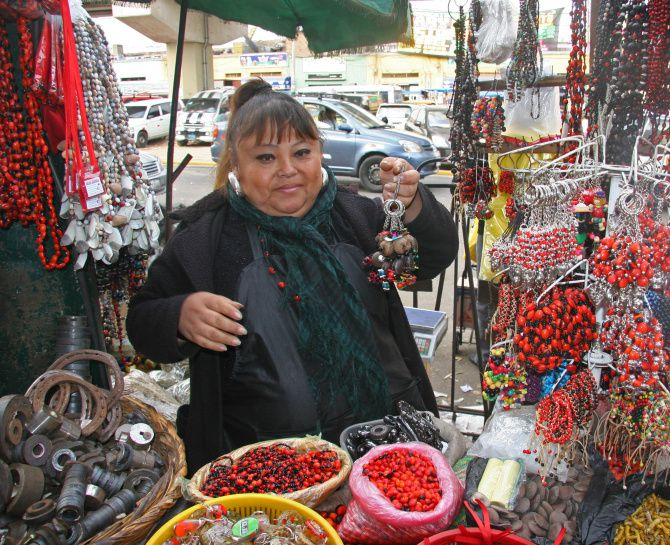 In this June 7, 2013 photo, Beatrice Torre sells items made from huayruro hembra and el macho, which are bright red and black Amazonian seeds, outside the witches market in Lima, Peru.