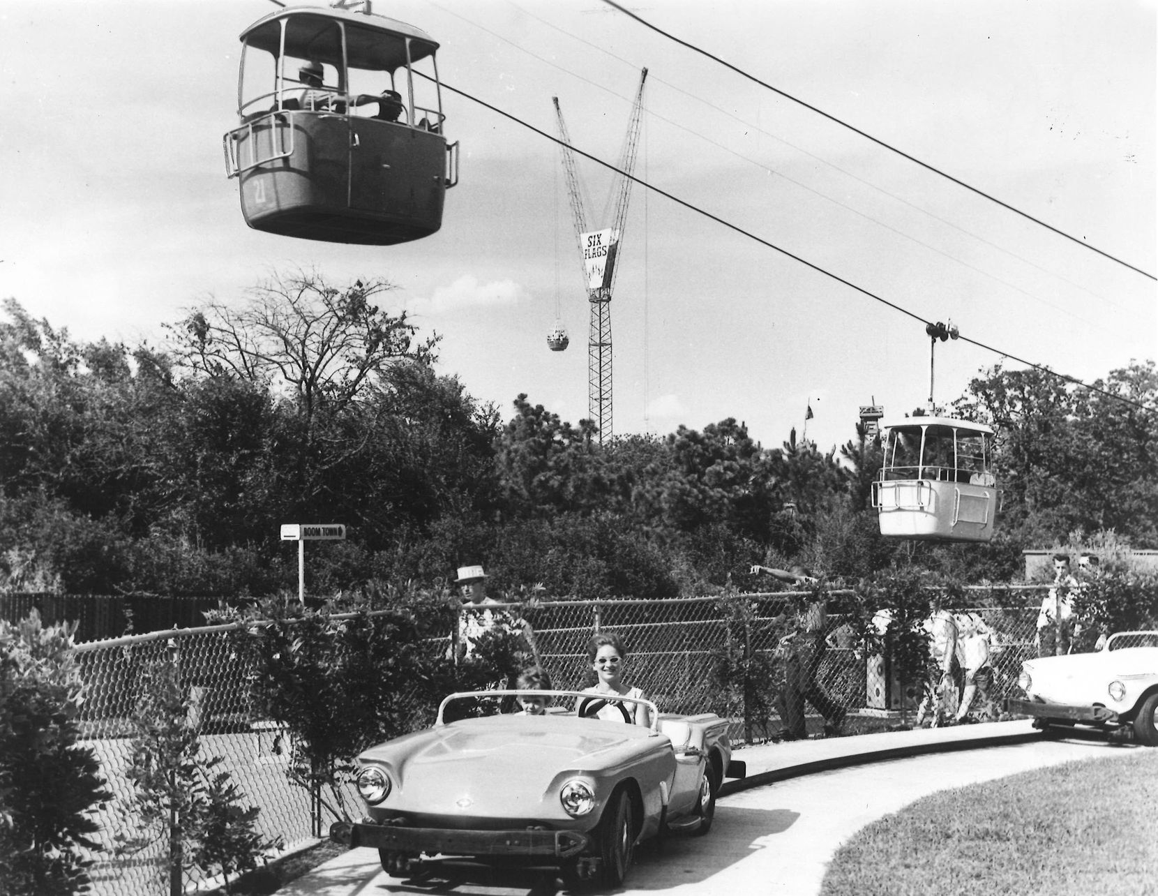 The Happy Motoring Speedway was a popular attraction at Six Flags as Patrons could slip behind the wheel of a then-futuristic, sleek sports car and drive around a modern highway that didn't involve honking  or passing cars as they could only ride in the middle lane.