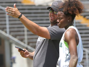 Mansfield Lake Ridge long jump and triple jump coach James Whisenhunt speaks with Jasmine Moore during the triple jump competition at the Class 5A Region II meet on  April 28, 2018. Moore won gold medals in that event and three others at regionals. (Steve Hamm/ Special Contributor)