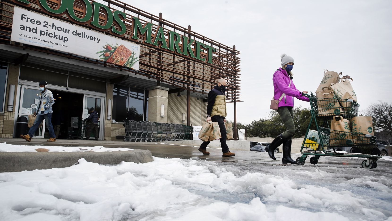 Shoppers push heir carts through the slush at Whole Foods Market in the Lakewood area of Dallas, Tuesday, February 16, 2021.