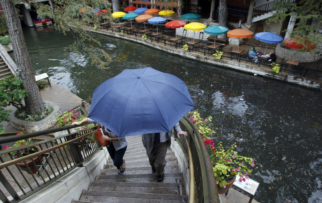 Visitors use an umbrella for protection from a light rain as they walk along the River Walk, Tuesday, Nov. 8, 2011, in San Antonio. (AP Photo/Eric Gay) 11092011xNEWS