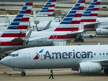 An American Airlines plane pushes back from the gate at Dallas Fort Worth International Airport Terminal C.