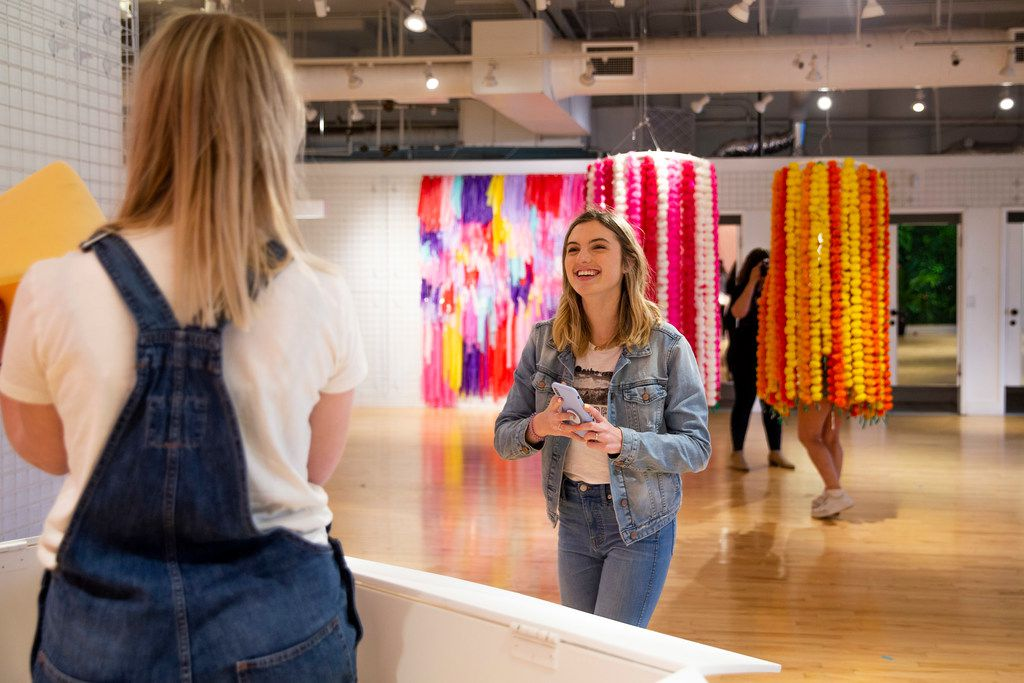 Ally Jacobs smiles before taking a picture of Ella Givens at the Snap151 in Dallas on Friday, April 5, 2019. Snap151 is an interactive photo studio. (Shaban Athuman/Staff Photographer)