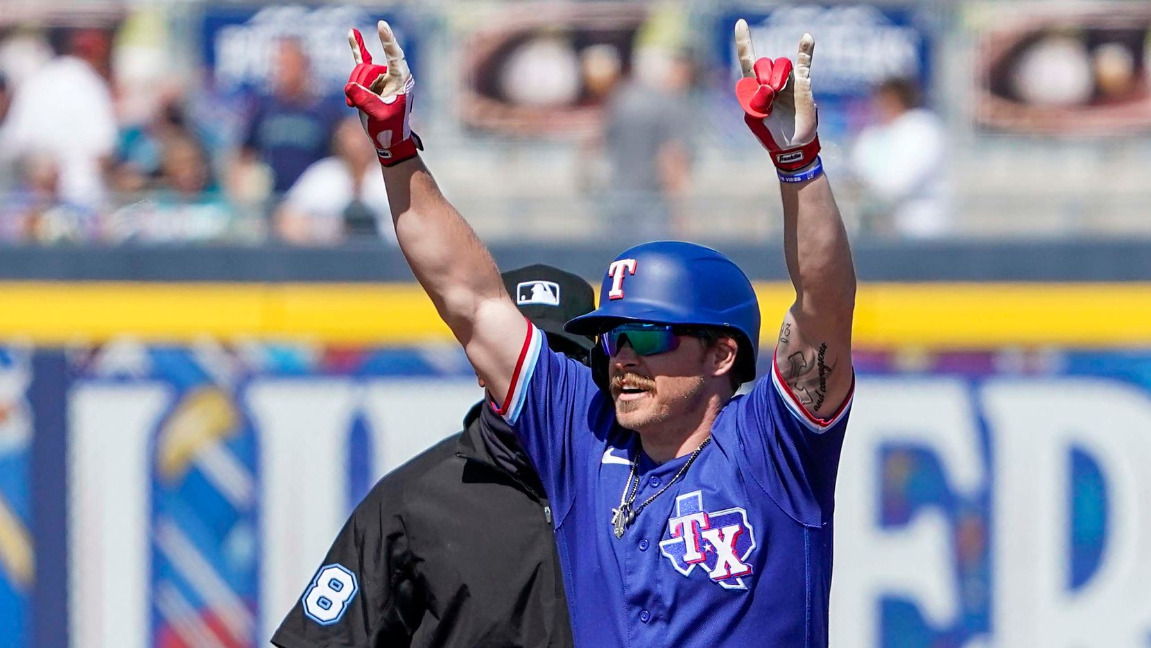 Texas Rangers infielder Brock Holt celebrates at second base after hitting a leadoff double during the first inning of a spring training game against the Seattle Mariners at Peoria Sports Complex on Wednesday, March 10, 2021, in Peoria, Ariz.