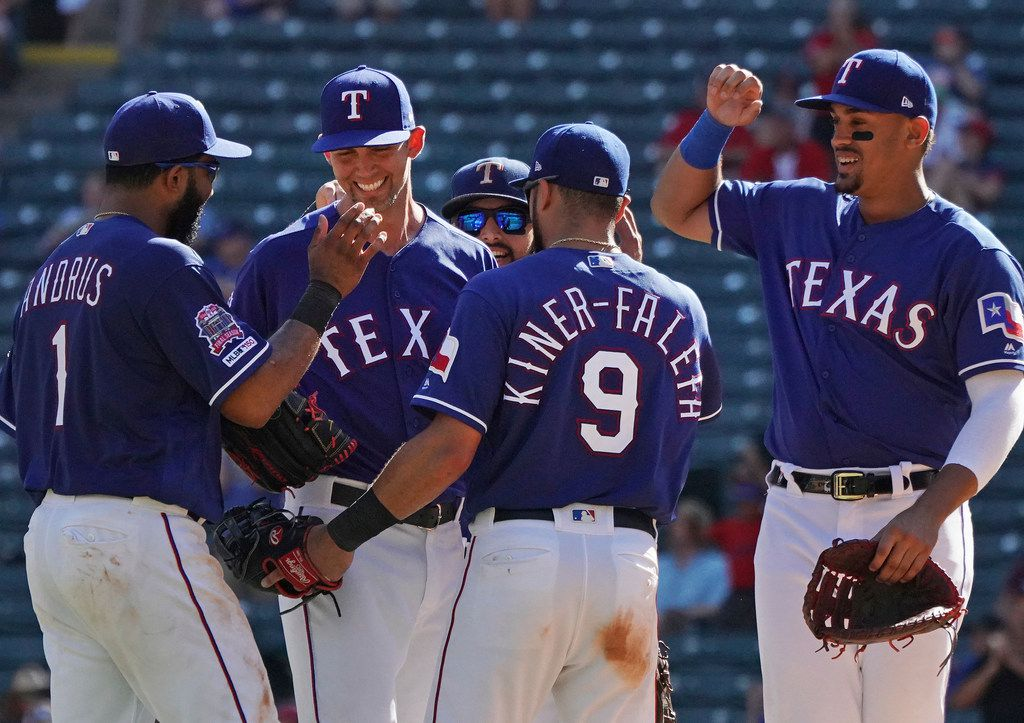 Teammates congratulate Texas Rangers starting pitcher Mike Minor, second from left, on the field after he recorded his 200th strikeout for the season in the ninth inning of a baseball game against the Boston Red Sox, Thursday, Sept. 26, 2019, in Arlington, Texas. (AP Photo/Louis DeLuca)
