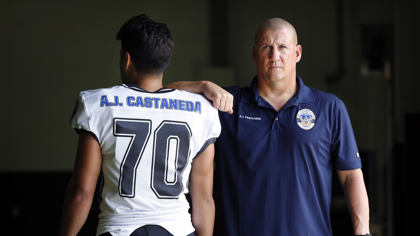 Arlington Martin senior linebacker Samuel Ledesma and head coach Bob Wager model the uniform and polo shirt the team will honor Friday in memory of Grand Prairie police officer A.J. Castaneda, who was killed in the line of duty in June. The special uniforms will have Castaneda's End of Watch badge on the jersey sleeve, and they will also have Castaneda's name on the back of the jersey. Martin will also have a decal on their helmets that recognize Castaneda. There will be a special ceremony before this Friday's game between Arlington Martin and Arlington to recognize Castaneda. Wager coached Castaneda when he was an assistant coach at Arlington Sam Houston and also when he was the head coach at Tolar High School. Wager also spoke at Castaneda's funeral. They are photographed at the school's indoor facility in Arlington, Texas, Tuesday, October 15, 2019.