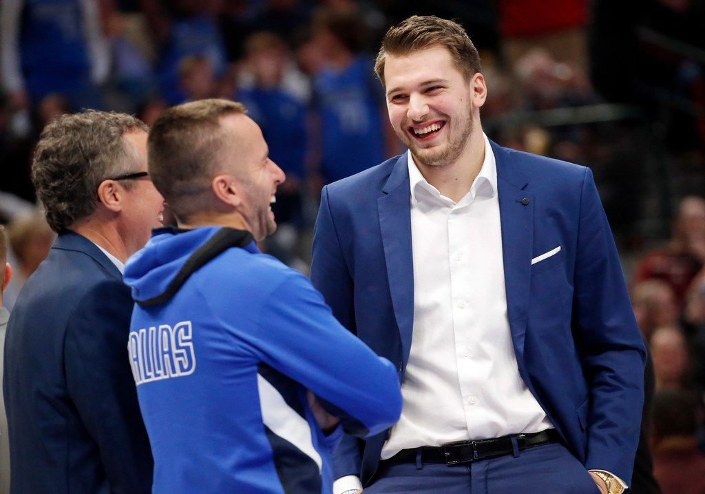 Dallas Mavericks forward Luka Doncic (right) laughs along with Dallas Mavericks guard J.J. Barea (center) during a second half timeout against the Boston Celtics at the American Airlines Center in Dallas, Wednesday, December 18, 2019. (Tom Fox/The Dallas Morning News)