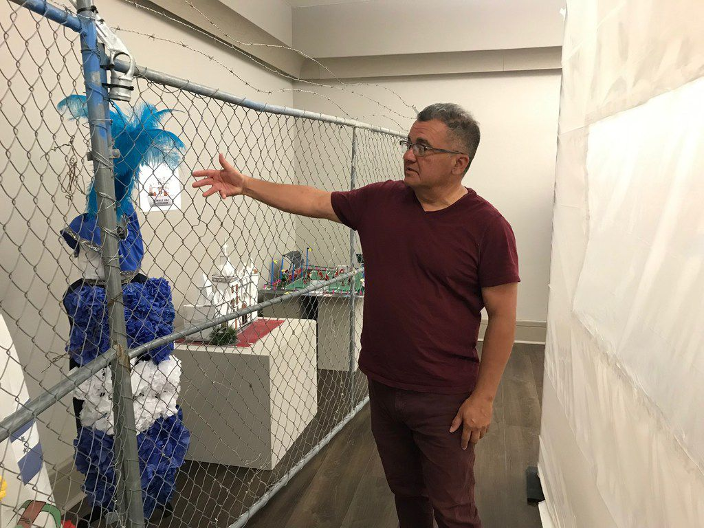 "El Paso historian David Romo is co-curator of the ""Uncaged Art"" exhibition, which opened at UTEP's Centennial Museum. He shows off a traditional dress made by Central American migrant youths whose work is on display in the ""Uncaged Art"" exhibition at UTEP's Centennial Museum."