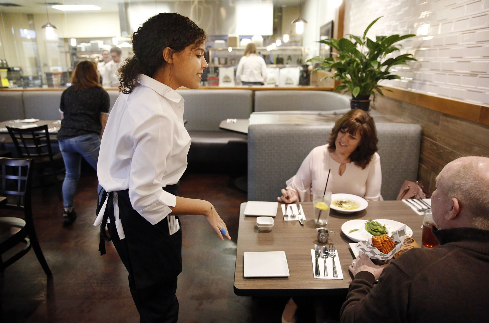 Culinary student Miranda Landis (left) serves Angela England (center) and her husband Chris England of Cedar Hill in the Savvy's Bistro at Ben Barber Innovation Academy in Mansfield.