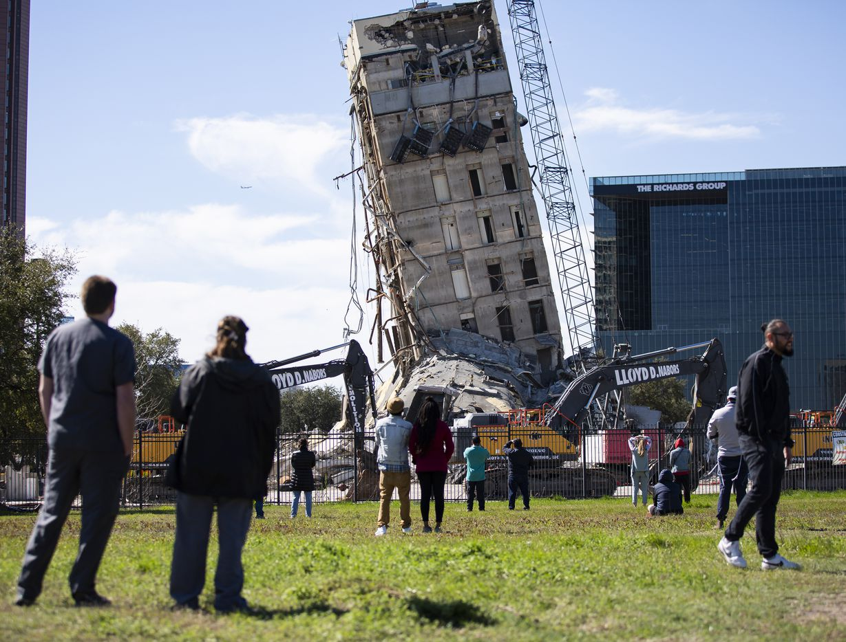 A crowd watches as Lloyd D. Nabors Demolition, LLC chips away at the top levels of the former Affiliated Computer Services building with a wrecking ball on Monday, Feb. 24, 2020 in Dallas. (Juan Figueroa/The Dallas Morning News via AP)