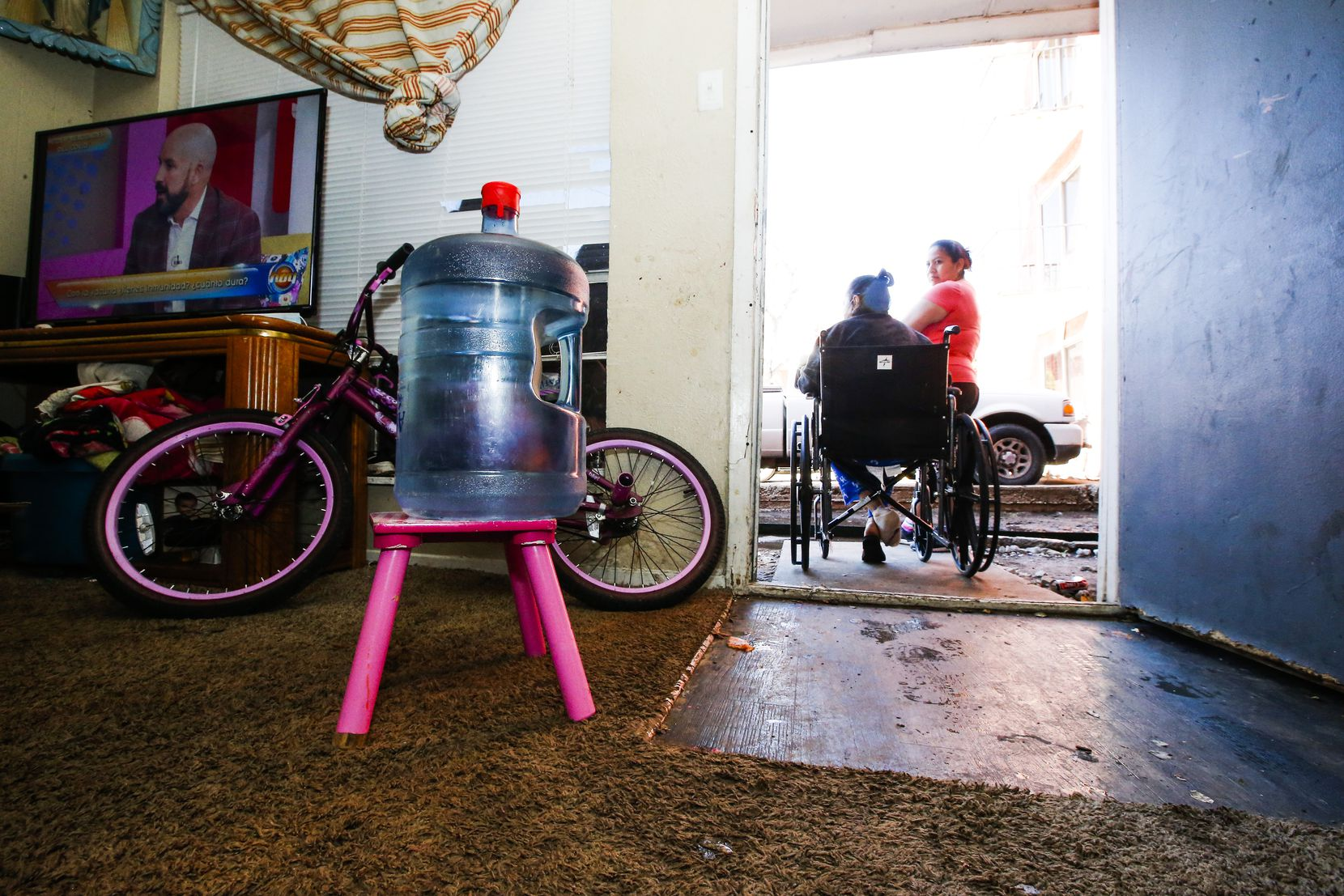 A water jug sat on a stool inside Modesta Gonzalez's home at the Villas del Solamar apartments in Dallas on Feb. 24, 2021. The apartments' water lines froze and broke in the severe cold last week, leaving residents without running water.
