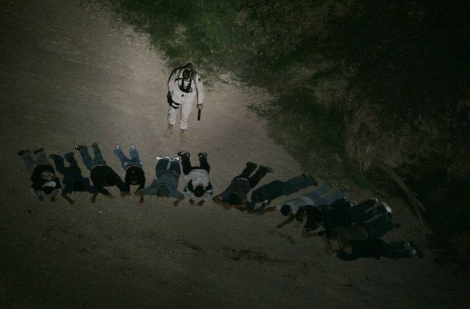 U.S. Border Patrol Borstar agent Dave Artz keeps watch on a group of 13 suspected illegal immigrants as a Blackhawk helicopter keeps a spotlight on the detained group found in the desert southwest of Tucson, Ariz., after a UAV Predator drone spotted the group with its aerial cameras.