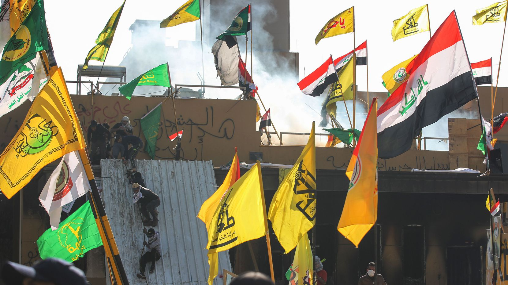 Supporters and members of the Hashed al-Shaabi paramilitary force try to scale a wall of the US embassy in the Iraqi capital Baghdad on January 1, 2020. Pro-Iran Iraqi demonstrators left the besieged US embassy in Baghdad after the Hashed al-Shaabi paramilitary force ordered them to withdraw.