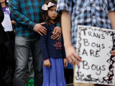 Libby Gonzales stands with her father, Frank Gonzales, as she joins other members of the transgender community during a rally on the steps of the Texas Capitol in early March. (AP Photo/Eric Gay)