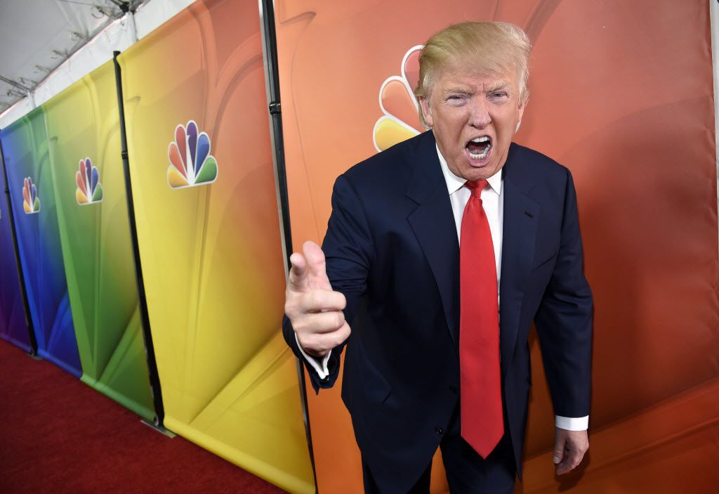 """In this 2015 photo, Donald Trump, then host of the television series """"The Celebrity Apprentice,""""mugged for photographers at the NBC 2015 Winter TCA Press Tour in Pasadena, Calif. NBC announced June 29, 2015, that it would end its business relationship with Trump over comments he made about immigrants when he announced his campaign for president. (Photo by Chris Pizzello/Invision/AP)"""