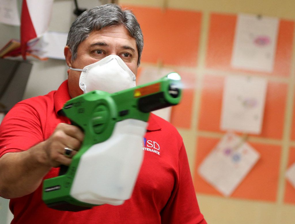 George Pedraza, a custodian with Garland ISD, sprays a disinfectant in a classroom at Parkcrest Elementary School in Garland on Feb. 8.