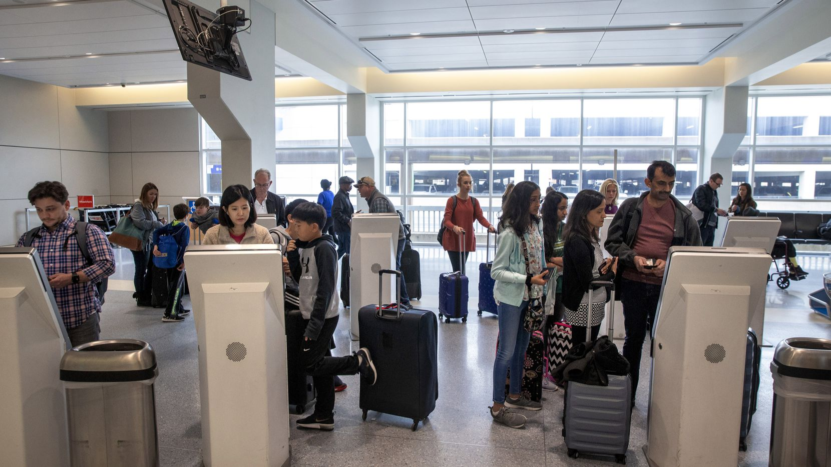 Passengers utilize the American Airlines electronic kiosks in the ticketing area of Terminal A at DFW International Airport in Irving, Texas, on Friday, November 22, 2019. American Airlines is making major changes to its apps and websites, including a system that lets customers make their own bids when a flight is overcrowded. (Lynda M. Gonzalez/The Dallas Morning News)