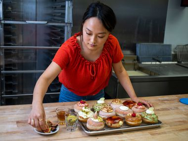 Jinny Cho, owner of Detour Doughnuts and Coffee, puts finishing touches on an assortment of doughnuts at Detour Doughnuts and Coffee in Frisco.