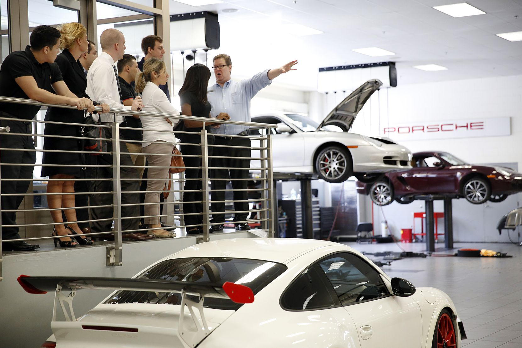 Training manager Patrick Gardner (right) leads a group of new employees on a tour of the Park Place Dealerships, including the Porsche service center, in Dallas, Thursday, August 21, 2014.  (Tom Fox/The Dallas Morning News)
