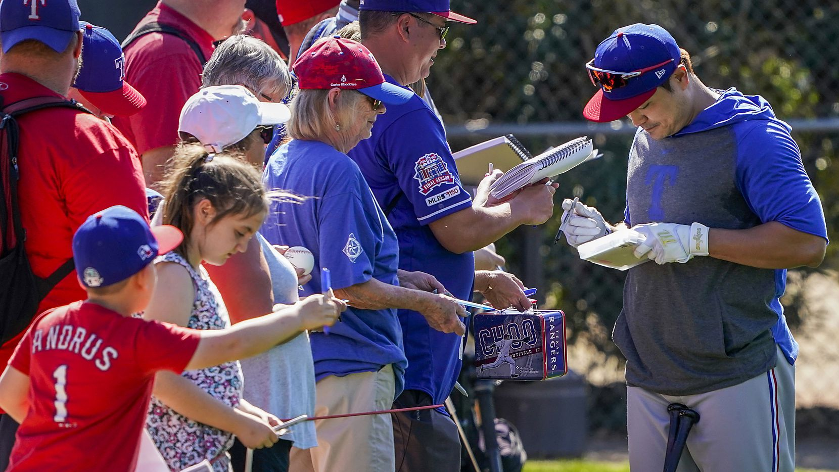 Texas Rangers outfielder Shin-Soo Choo signs autographs during a spring training workout at the team's training facility on Thursday, Feb. 20, 2020, in Surprise, Ariz.