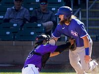 Texas Rangers infielder Davis Wendzel is out at home as Colorado Rockies catcher Chris Rabago applies the tag during the seventh inning of a spring training game at Salt River Fields at Talking Stick on Wednesday, Feb. 26, 2020, in Scottsdale, Ariz.