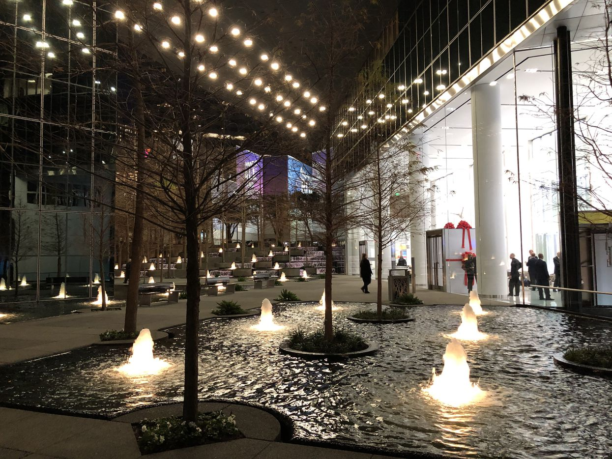 The fountains and trees surrounding the Ross Avenue tower now face a new retail strip.