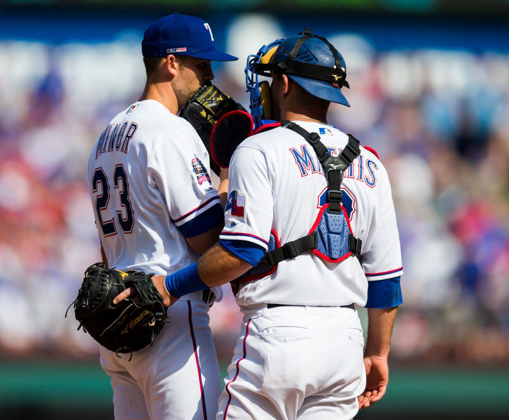 Texas Rangers starting pitcher Mike Minor (23) and catcher Jeff Mathis (2) conference on the mound during the fifth inning of an opening day MLB game between the Texas Rangers and the Chicago Cubs on Thursday, March 28, 2019 at Globe Life Park in Arlington, Texas. (Ashley Landis/The Dallas Morning News)