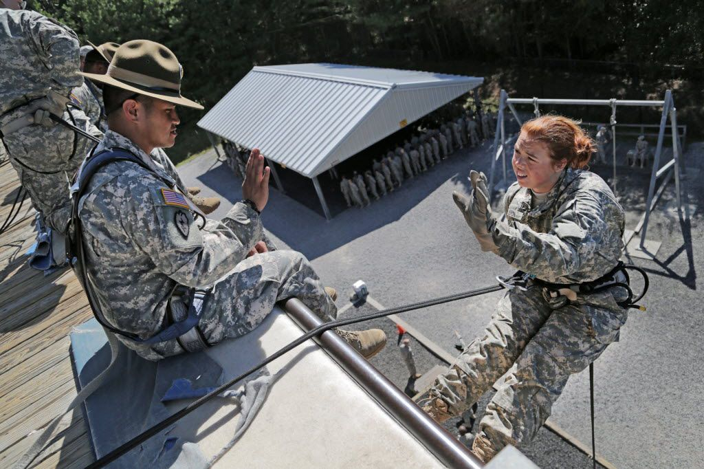 Drill Sergeant Ramil Preiksaitis waves at a private as she prepares to rappel the wall at Victory Tower at Fort Jackson in Columbia, S.C. New soldiers are required to complete the rope course as part of their basic training. The climbing and rappelling exercises on the 40-foot tower are intended to instill confidence in the soldier, and drill sergeants offer encouragement and precise directions.