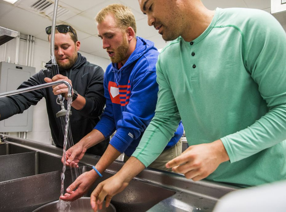 Minor league catcher Chuck Moorman, minor league pitcher Reed Garrett and Texas Rangers starting pitcher Eddie Gamboa (78) wash potatoes during a spring training cooking class at the team's training facility on Thursday, February 23, 2017 in Surprise, Arizona. (Ashley Landis/The Dallas Morning News)