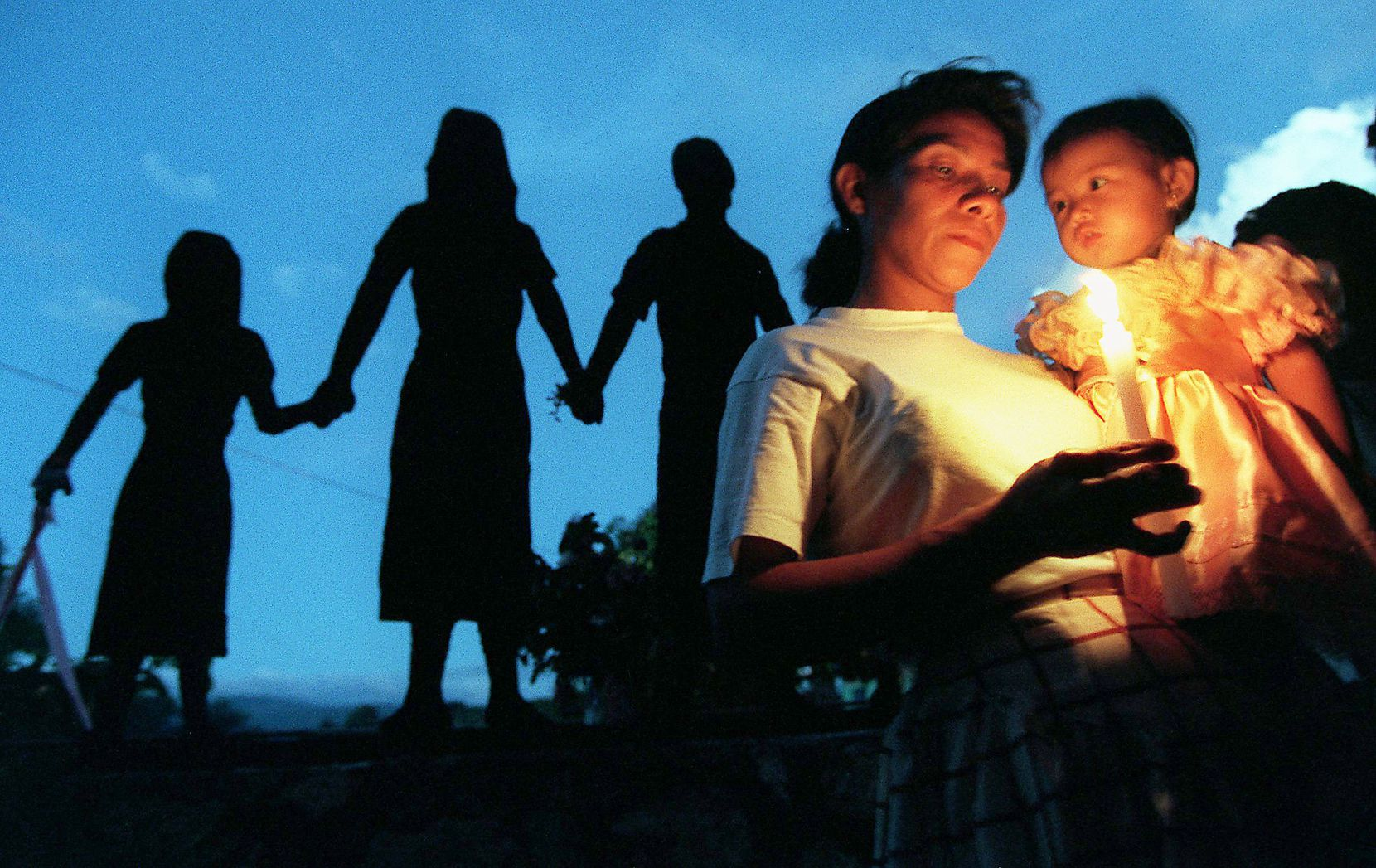In 1997, Maria Christina Chicas held her grandaughter, Mirllama Clara Luz, 1, during a candlelight vigil on All  Soul's Day at El Mozote, El Salvador, site of a massacre of an entire village by Salvadoran Army soldiers in 1981 during the  guerilla war. She lost three sisters and a borther and nine of their children in the massacre. The silhouettes are part of a monument at the massacre site.
