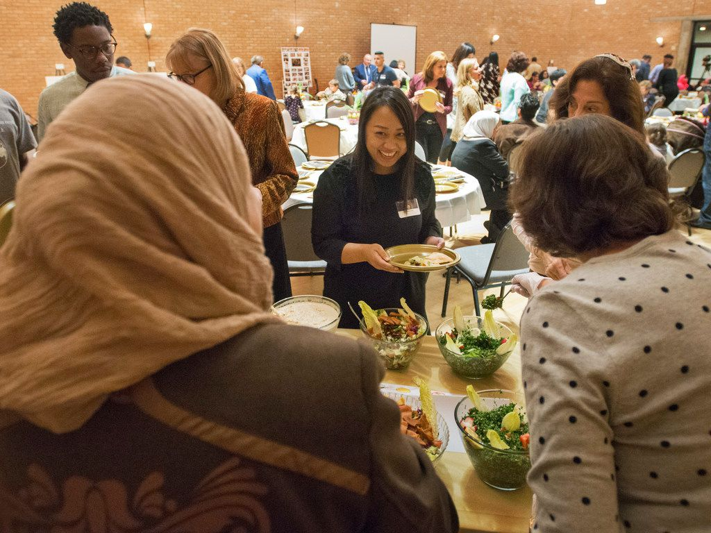 Mariam Alshiblaq, a Syrian refugee, left, laughs with a guest at the Leah's Kitchen annual Thanksgiving Community Meal at Temple Emau-El in Dallas Nov. 16.