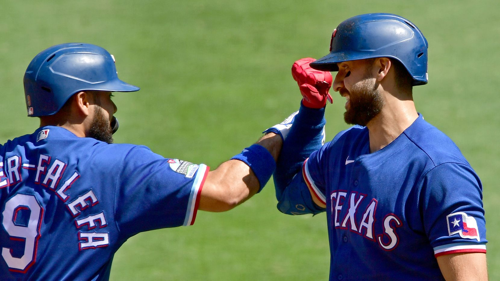 ANAHEIM, CA - SEPTEMBER 21: Isiah Kiner-Falefa #9 of the Texas Rangers is congratulated by Joey Gallo #13 after hitting a solo home run in the first inning against the Los Angeles Angels at Angel Stadium of Anaheim on September 21, 2020 in Anaheim, California.